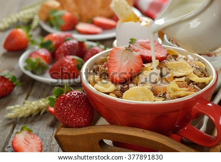 Muesli with strawberries on a wooden background - stock photo
