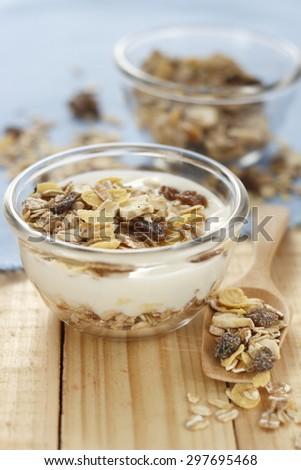 muesli with yogurt on blue cotton place on wooden background. multi fruit and multi grain muesli. - stock photo