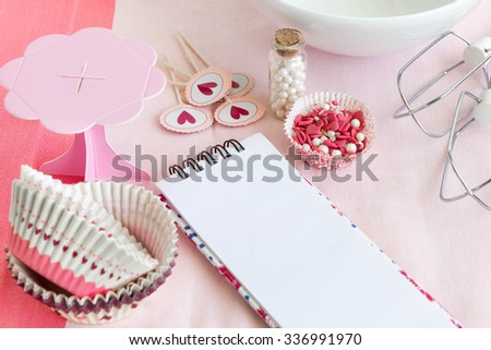 Muffin baking utensils with emtpy notebook for recipe - stock photo