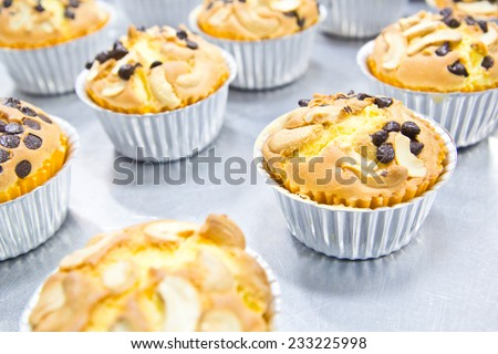 Muffin butter cakes with cashew nut and chocolate chips on top - stock photo
