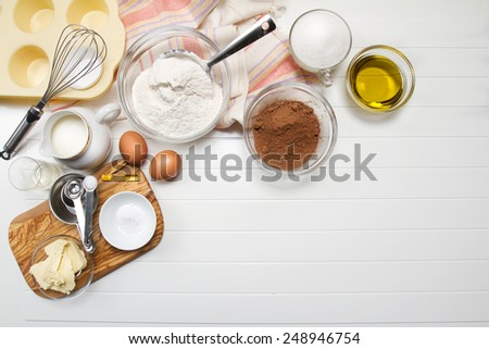 Muffin ingredients: milk, flour, sugar, eggs, butter, olive oil, cocoa powder, baking soda, vanilla extract and vinegar - stock photo