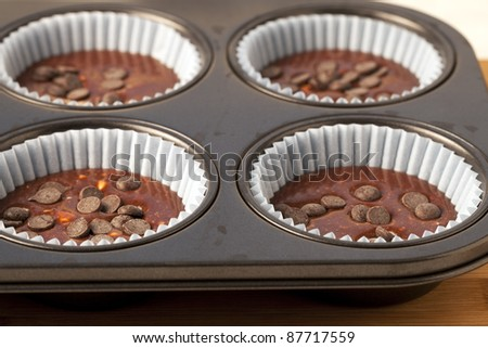 Muffin pan with chocolate batter and chocolate chips. - stock photo