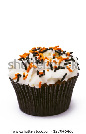Muffin with white icing decorated with sprinkles displayed over white background. - stock photo