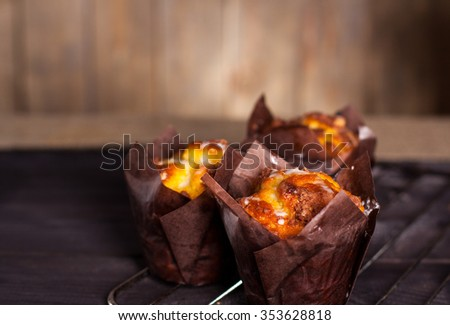 Muffins witch chocolate on wooden background.