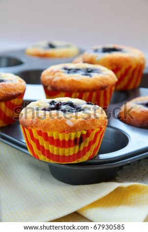 Muffins with berries on a yellow napkin