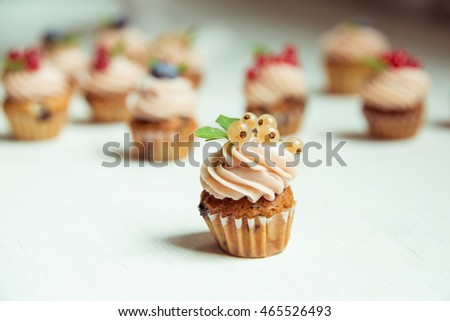 Muffins with cranberries, blueberries and currants in the foreground on a white wooden table. Side view