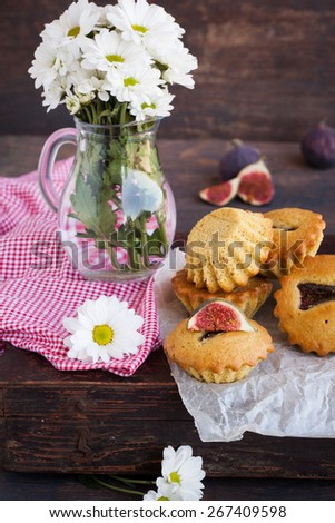 Muffins with figs.Jug of flowers. - stock photo