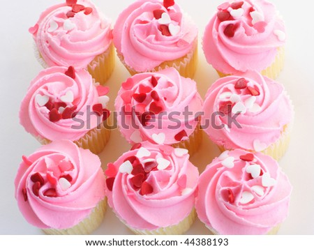 Muffins with pink colored frosting sprinkled with heart shaped candy on top - stock photo