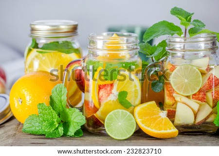 Mug delicious refreshing drink of mix fruits with mint on wooden, infused water - stock photo