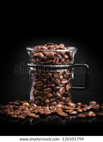 Mug made of glass with roasted coffee beans on black background - stock photo