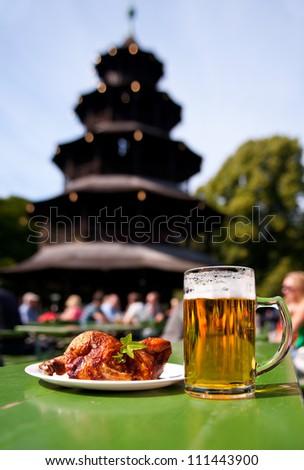Mug of beer and half chicken against Pagoda in English Garden, Munich, Bavaria, Germany - stock photo
