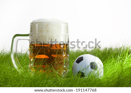 mug of beer and soccer ball on grass in white background - stock photo