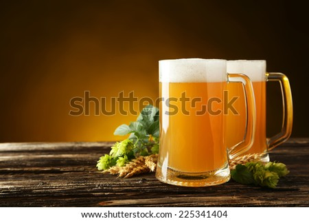 Mug of beer on a brown wooden background