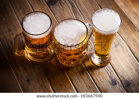 Mug of beer on wooden background - stock photo