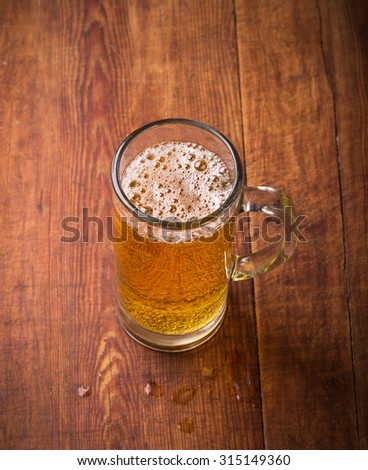 Mug of beer on wooden  background. - stock photo