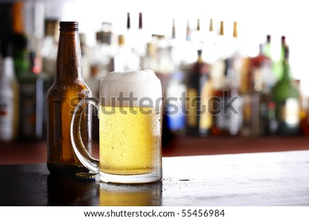 Mug of beer with bottle shot in tavern - stock photo