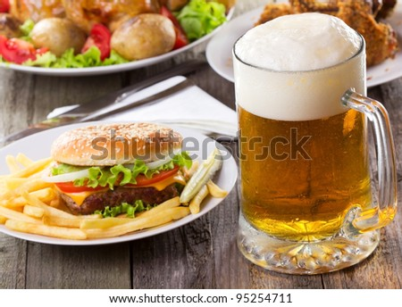 mug of beer with hamburger and fries - stock photo
