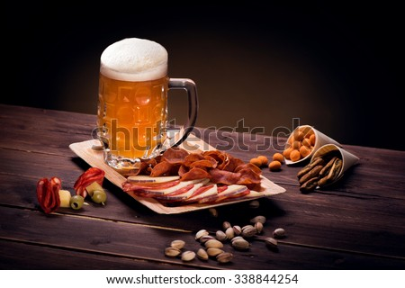 Mug of beer with snacks on wooden table