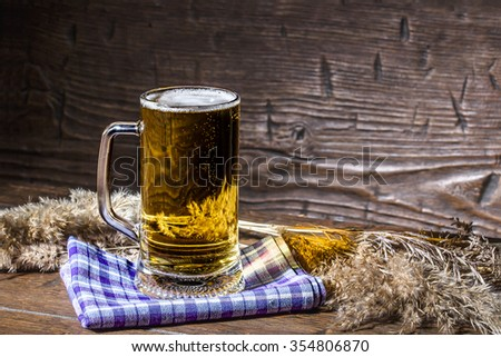 Mug of cold beer is standing on the checkered  napkin on vintage table among dry stalks - stock photo