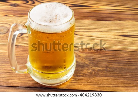 Mug of cold beer on wooden table, close-up view - stock photo