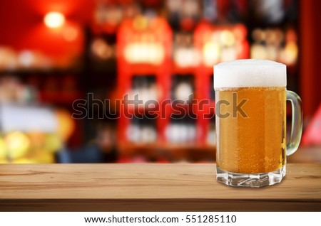 Mug of cold beer with foam on wooden table in pub