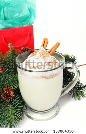Mug of delicious Holiday egg nog on white background with pine boughs and a Christmas gift.   - stock photo