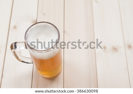 Mug of draft beer on wooden table  - stock photo