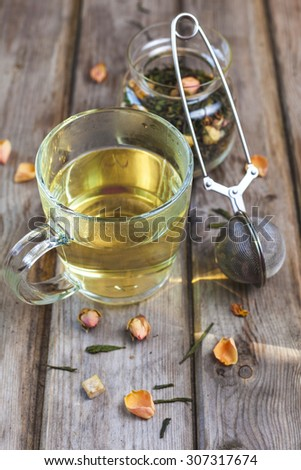 Mug of flavored green tea with rose buds and petals on wooden rustic table - stock photo
