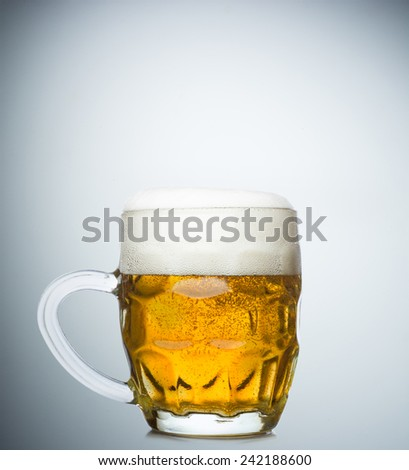 Mug of fresh beer with cap of foam isolated on white background - stock photo