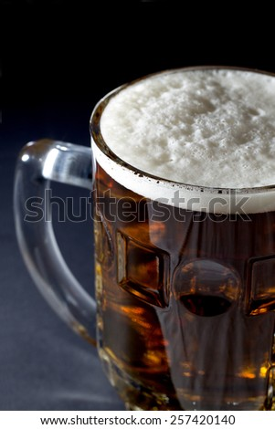 Mug of Fresh Beer with Foam Over Black Background Closeup - stock photo