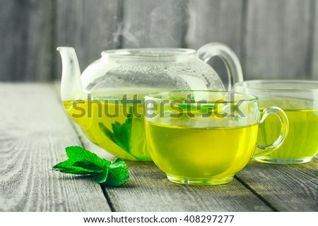 Mug of green tea and teapot on wood table