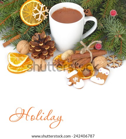 Mug of hot chocolate and dried oranges against fir-tree branches.
