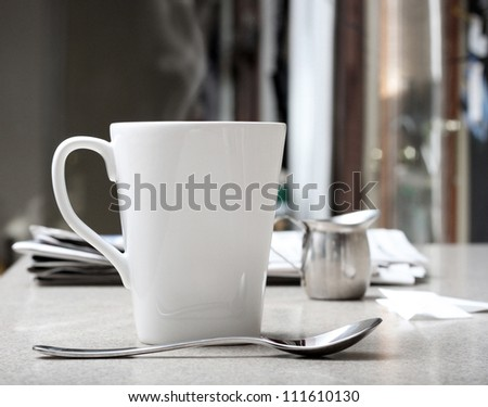 Mug of hot coffee or tea with stainless creamer and morning newspaper on counter. Intentionally desaturated for effect - stock photo
