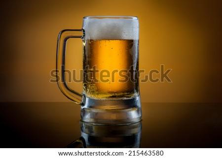 Mug of lager beer on black  table - stock photo