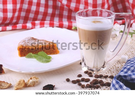 Mug of latte and piece of carrot pie on the decorated coffee table with rural napkins. Desert in the stylish interior with coffee beans and vintage tablecloths. - stock photo