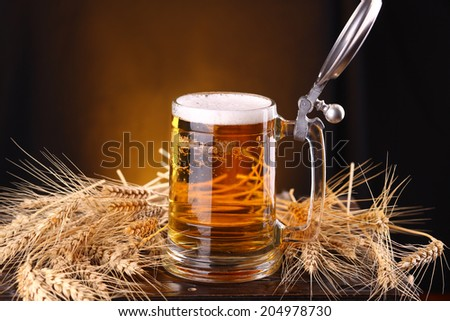 Mug of light beer on a wooden chest with barley ears - stock photo
