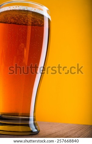 Mug of light beer on wooden table - stock photo