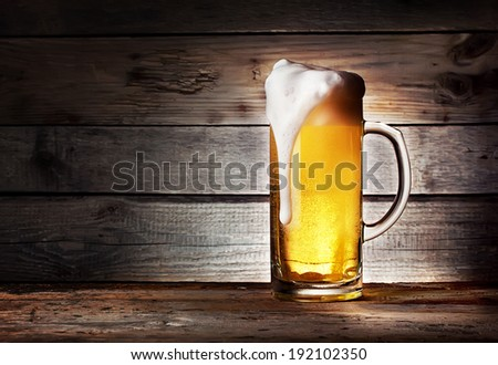 Mug of light beer with foam on wooden table - stock photo