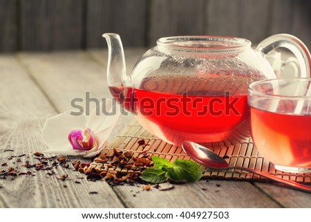 Mug of red tea and teapot on wood table