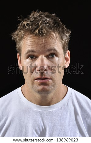Mug shot of Caucasian man with messy blond hair in white t-shirt on black background