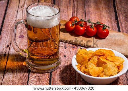 Mug with beer on the old wooden bar table with potato chips and cherry tomatoes - Close up photo - stock photo
