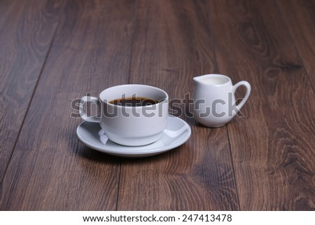 Mug with black coffee and milk jug on the wooden background