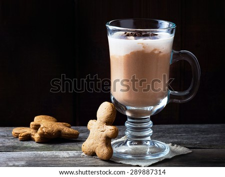 Mug with hot chocolate and foamed milk. Served with gingerbread man cookies on wooden table - stock photo