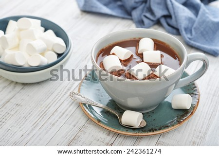 Mug with hot chocolate and marshmallows on wooden table - stock photo