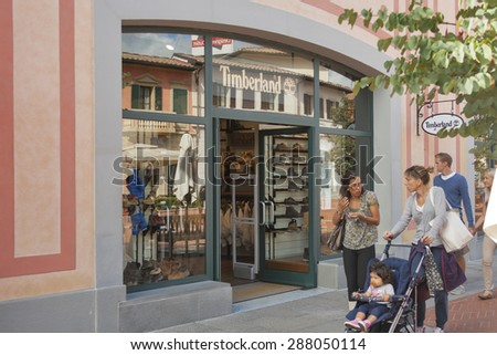 MUGELLO, ITALY - SEPTEMBER 11, 2014: People walk along Timberland store in McArthurGlen Designer Outlet Barberino. Timberland LLC is an American manufacturer and retailer of outdoors wear. - stock photo