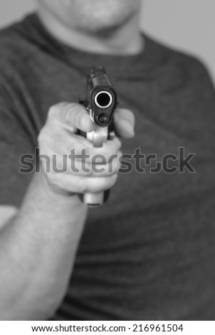 Mugger points his gun at his victim - stock photo