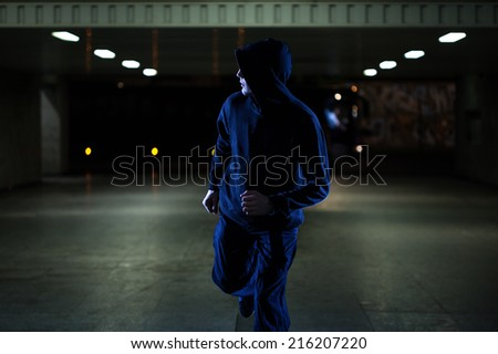 Mugger running in the underpass at night - stock photo