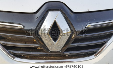 MUGLA ,TURKEY - JUNE 27, 2017: White Dirty Renault logo close up in Mugla. Renault S.A. is a French car manufacturer producing cars, vans, buses, trucks, tractors, tanks, autorail vehicles.