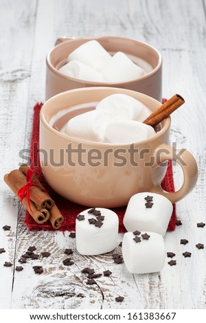 Mugs of hot chocolate with marshmallows and cinnamon sticks on a white wooden background