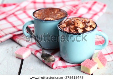 Mugs of hot coffee with marshmallow on napkin and color wooden table background - stock photo